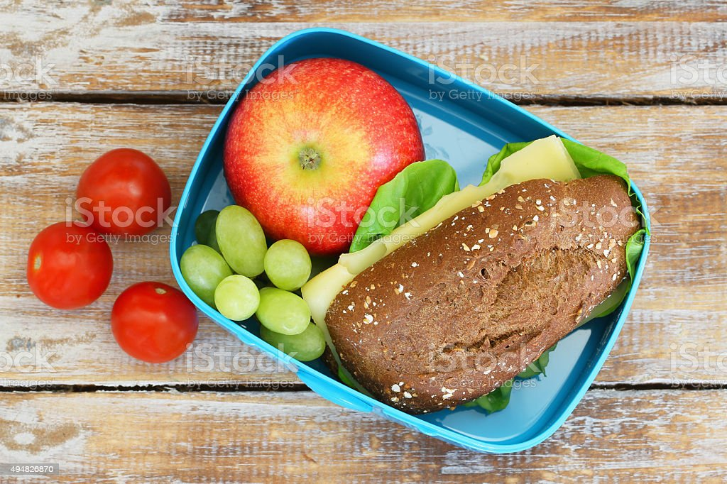 Lunch box consisting of wholegrain cheese sandwich, fruit, cherry tomatoes stock photo