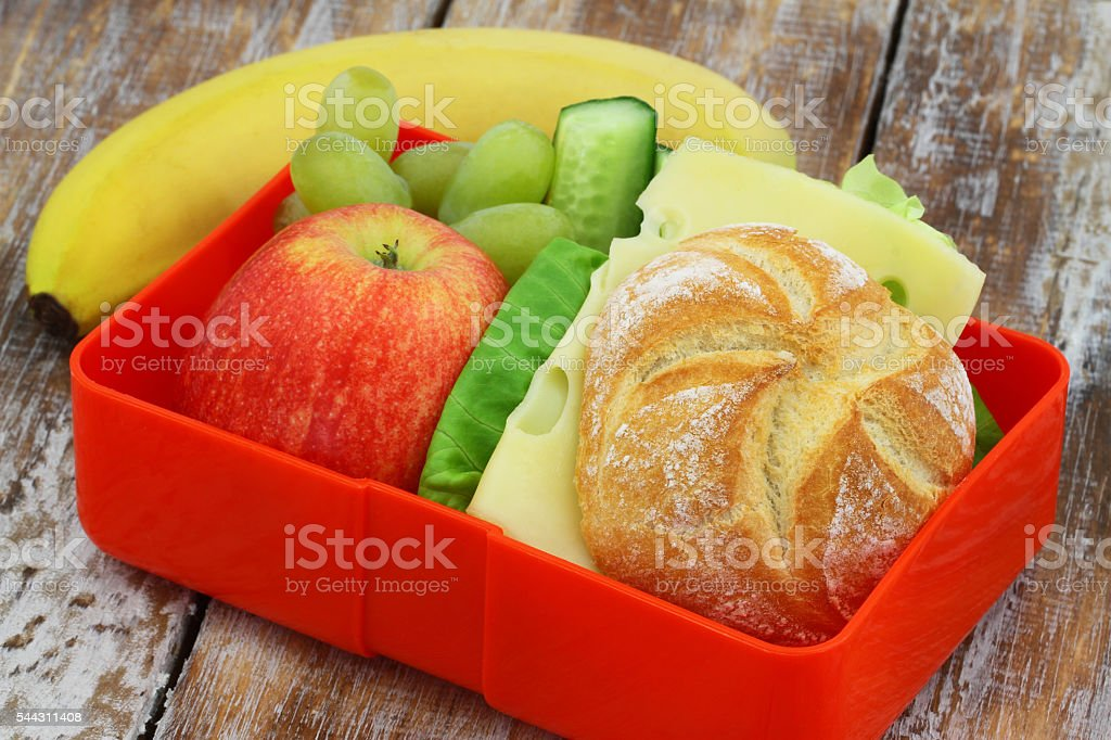 Lunch box containing cheese sandwich, apple, grapes and banana stock photo