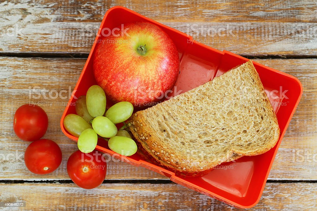 Lunch box with brown bread sandwich, apple, grapes and tomatoes stock photo