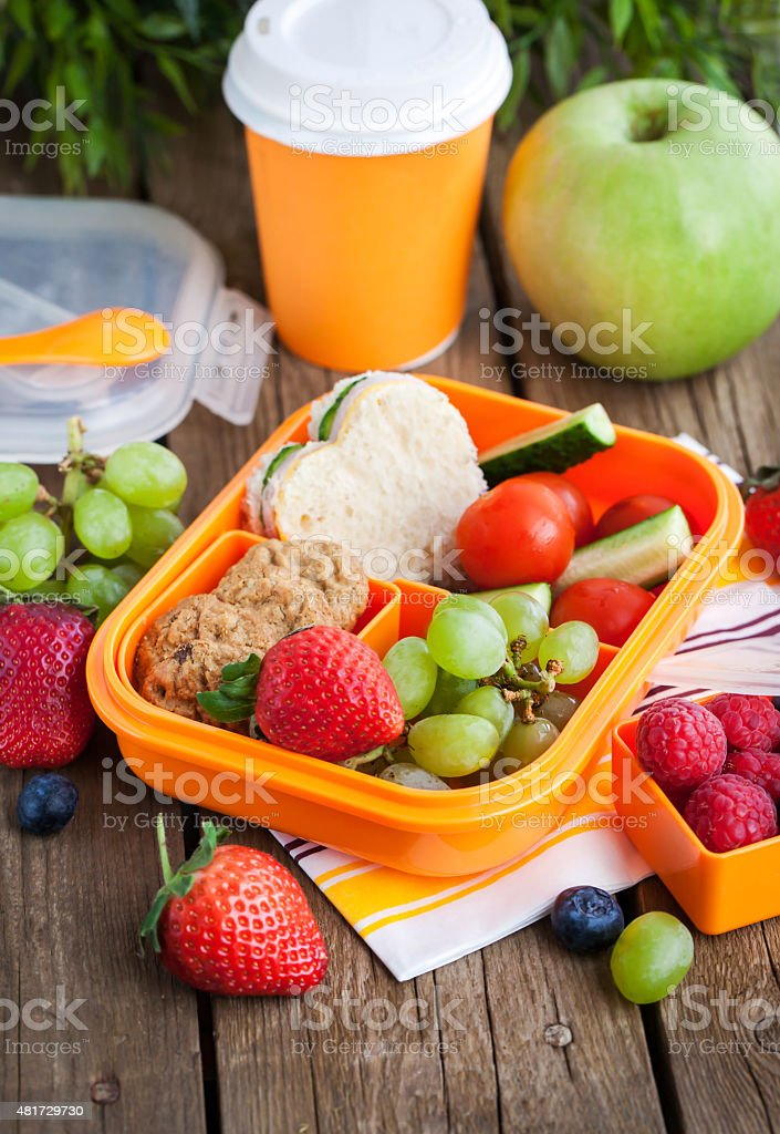 Lunch box with sandwich, cookies, veggies and fruits stock photo
