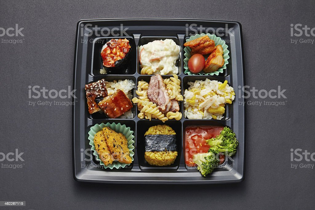 Lunch box with sushi and rolls isolated on black stock photo