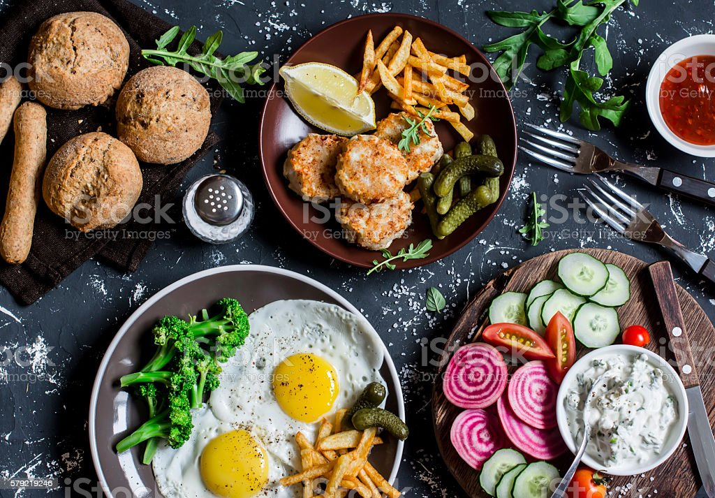 Lunch table - fried eggs, fish balls, potato chips, vegetables stock photo