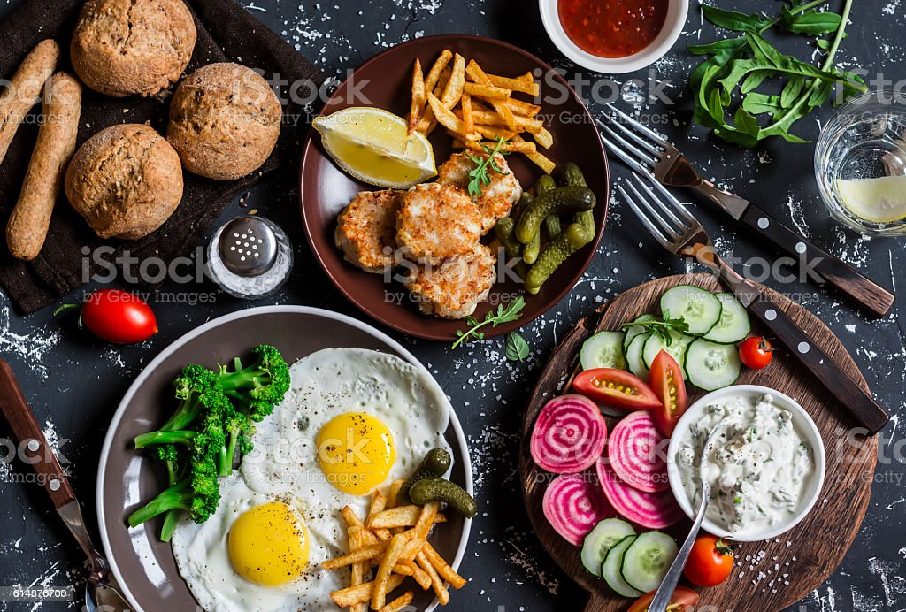 Lunch table - fried eggs, fish balls, potato, vegetables, sauces stock photo