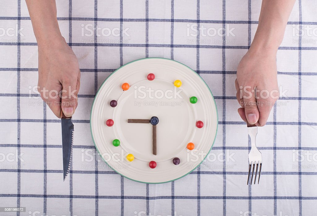 Lunch time concept, clock in plate, knife and fork stock photo