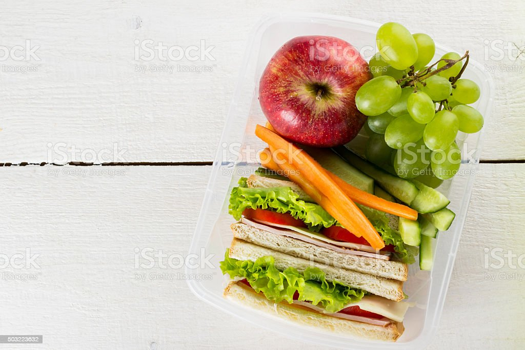Lunchbox with sandwich, vegetables, fruit on white background stock photo