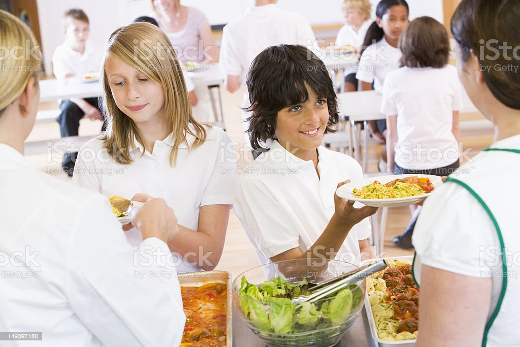 Lunchladies serving plates of lunch in school cafeteria stock photo