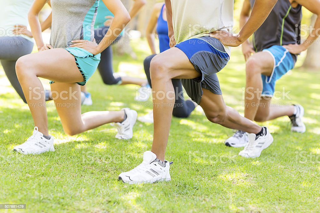 People Doing Lunges In Park stock photo