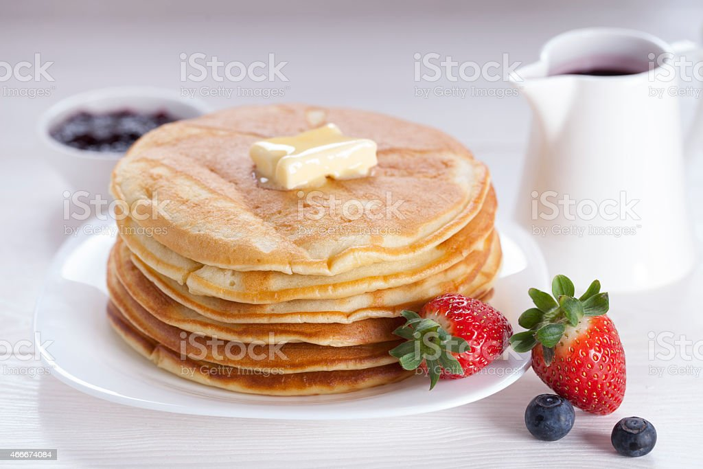 Luscious fluffy pancakes with sweet berries on white plate  stock photo