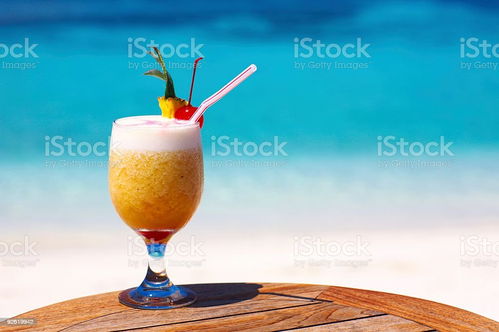 Luscious tropical drink, perched beachside atop a table royalty-free stock photo