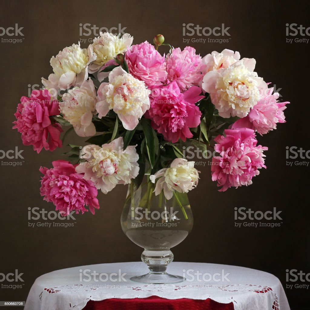 Lush bouquet of pink peonies in a vase on the table. stock photo