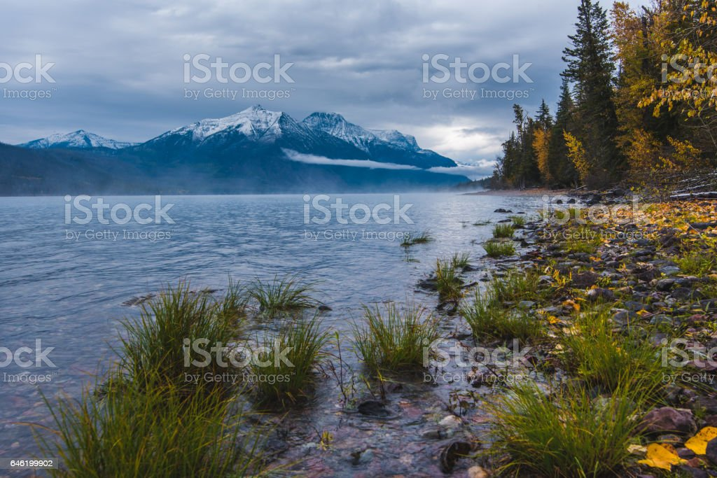 Lush lake coast overlooking snowcapped mountains. stock photo