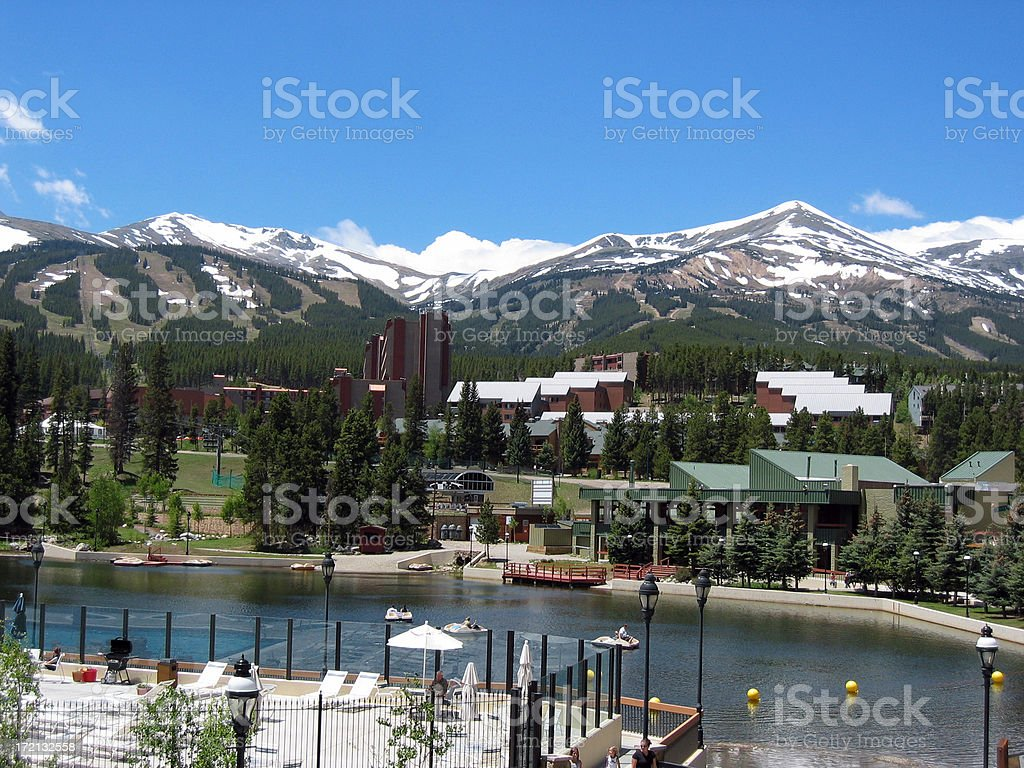 Lush summer resort facing snowy mountains in the distance stock photo