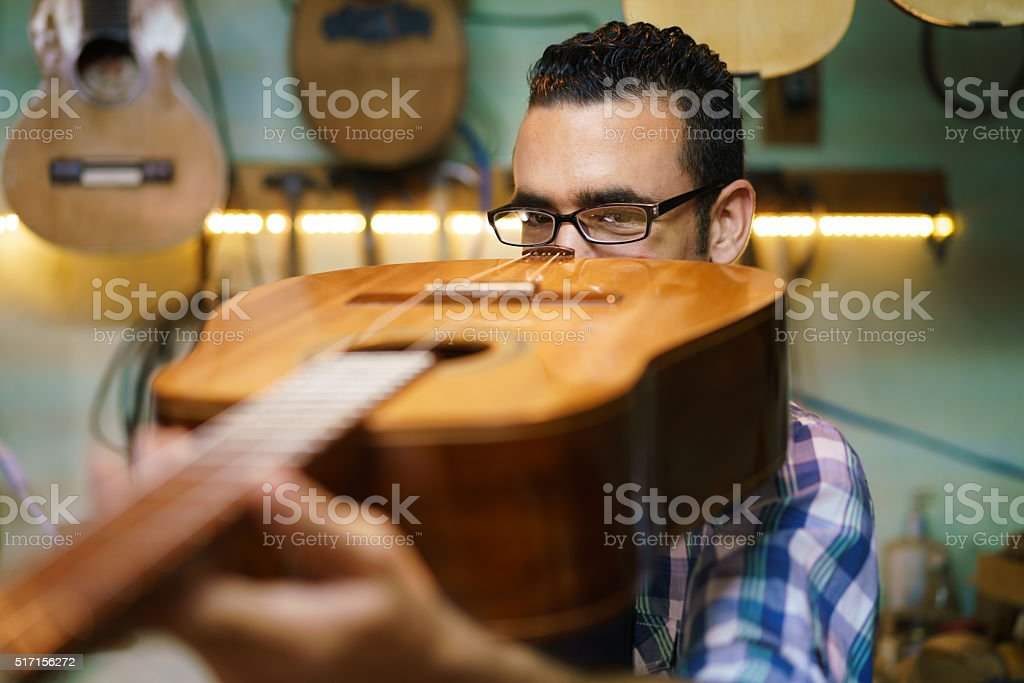 Lute Maker Checking Bridge And Arm Of Classic Guitar stock photo
