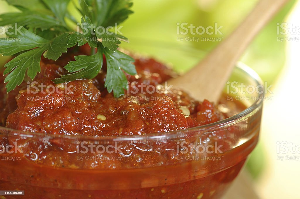 Lutenica in a clear bowl with wooden spoon and garnish in it stock photo