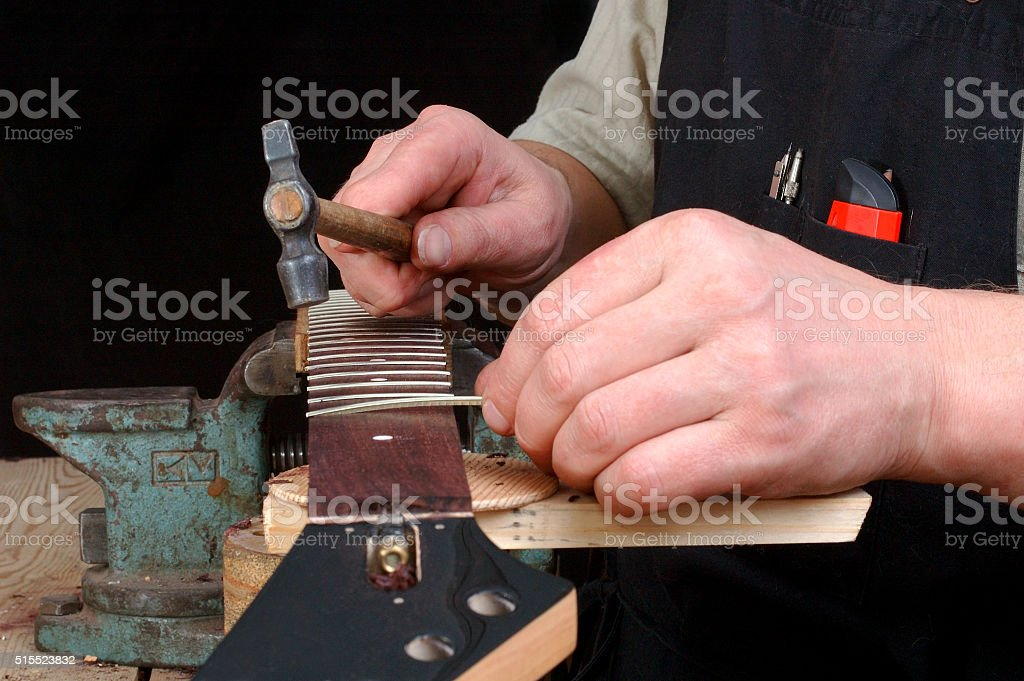 Luthier establishes frets in a signature stamp stock photo