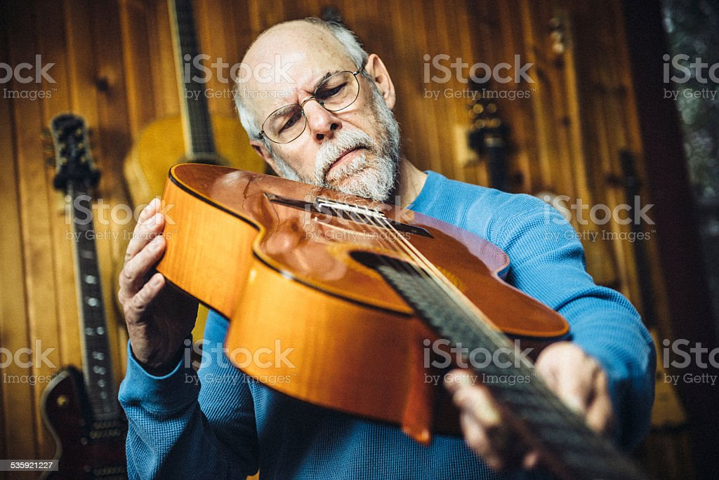 Luthier examining a classic guitar in workshop stock photo