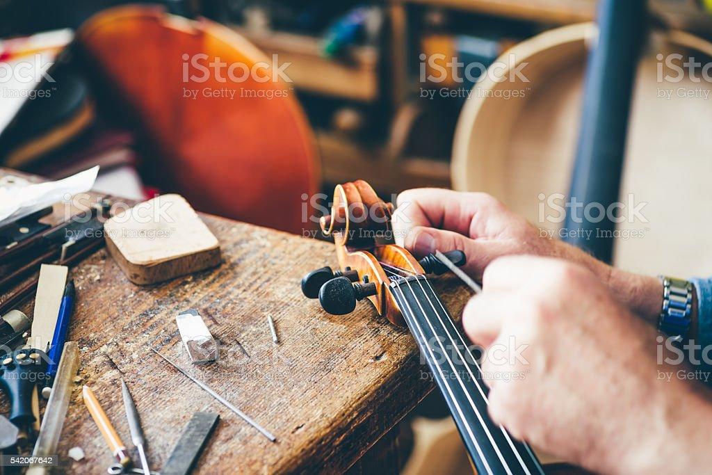 Luthier repair violin in his workshop stock photo