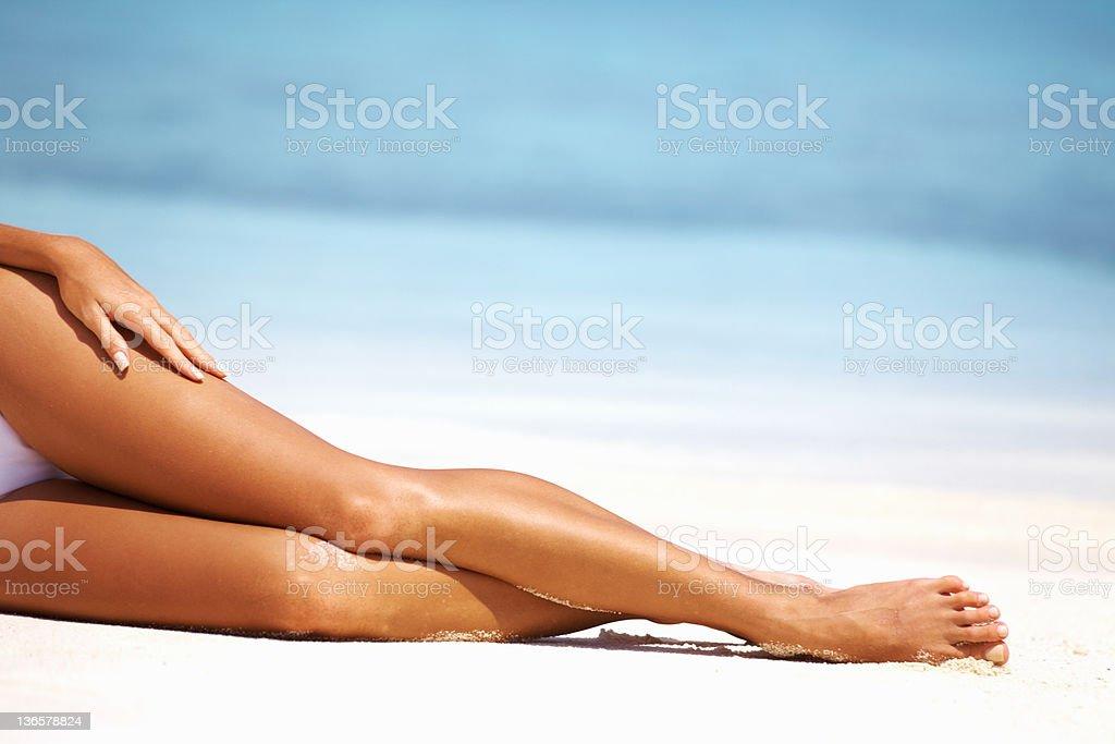 Luxuriant legs on the sand stock photo