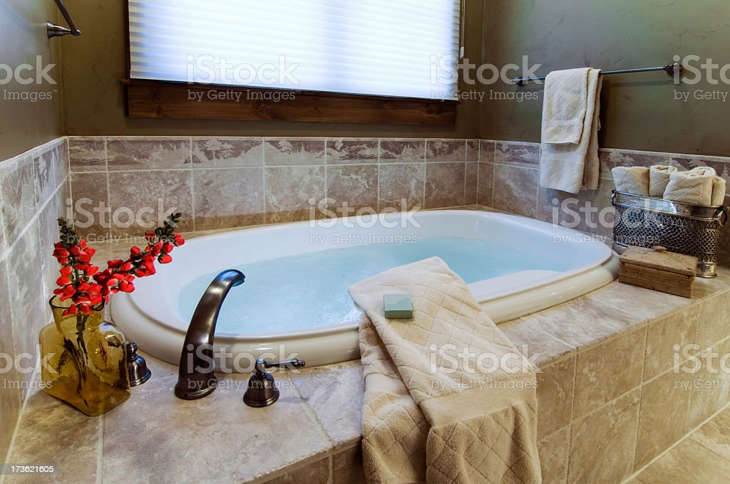 A luxurious bath with towels and flowers royalty-free stock photo