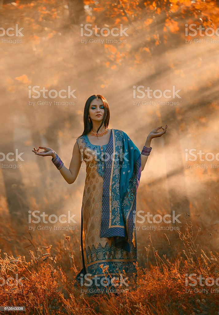 Luxurious Indian woman meditates standing outdoors in the sunlig stock photo