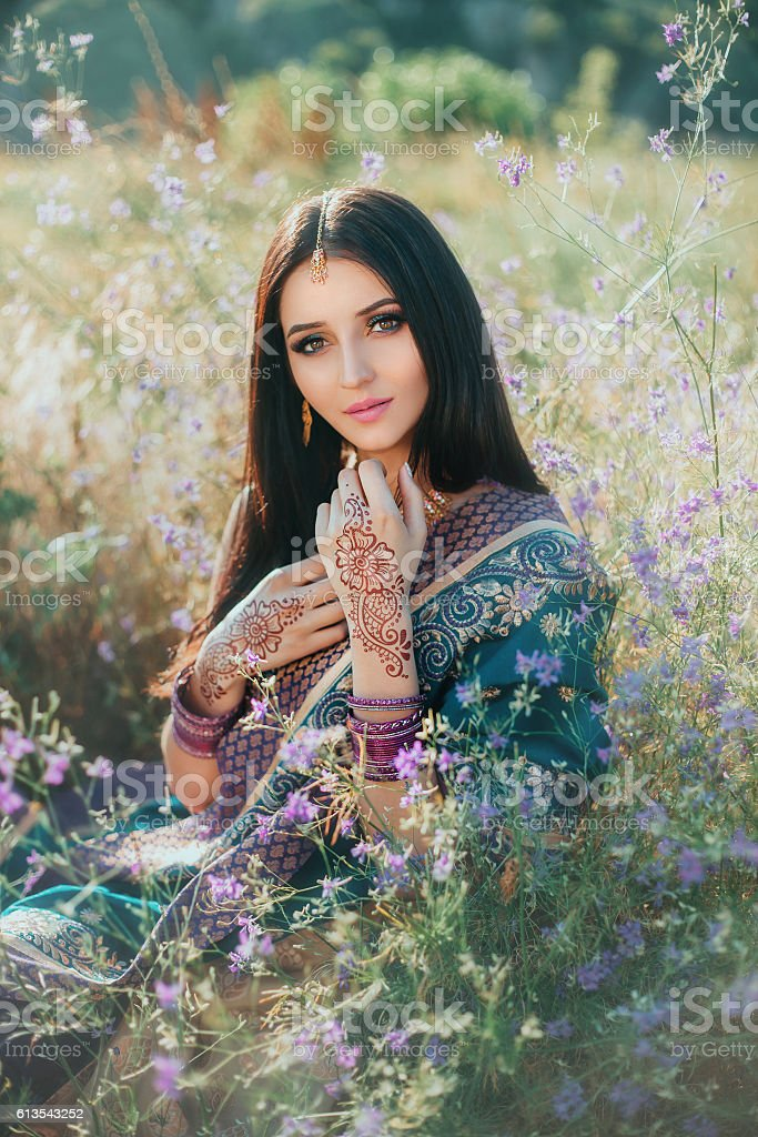 Luxurious Indian woman sitting in field  flowers on natural, dre stock photo