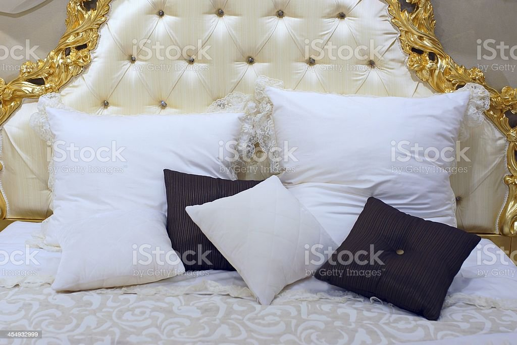 Luxurious king-size bed with gold-patterned headboard