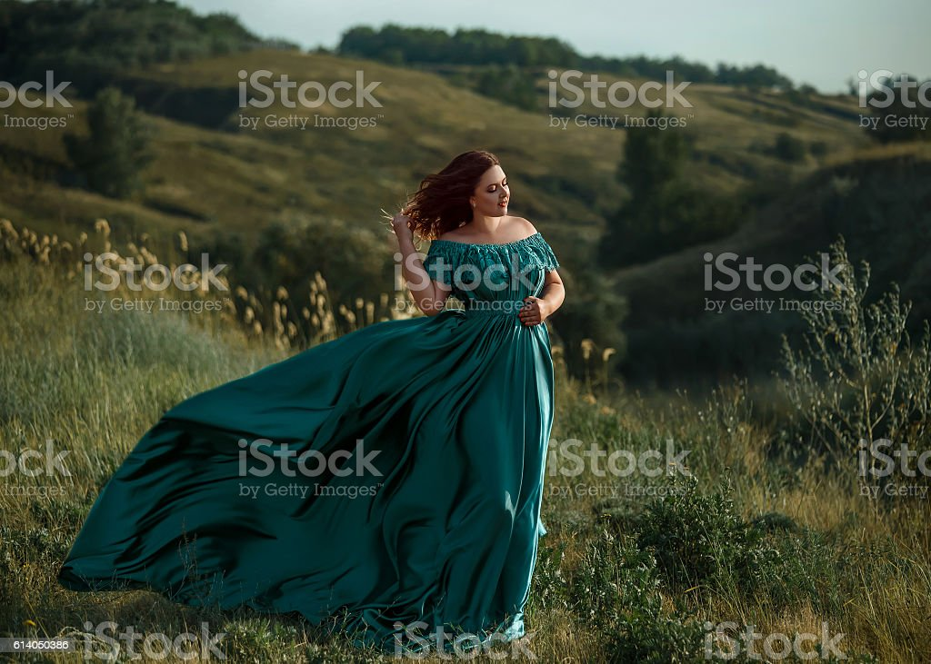 Luxurious lady in long green dress with bare shoulders. stock photo