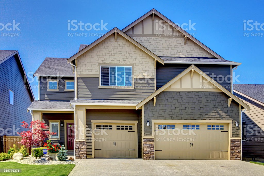 Luxurious modern house with two garage spaces and driveway. stock photo