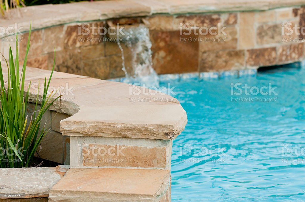 Luxurious swimming pool with stone waterfall. stock photo