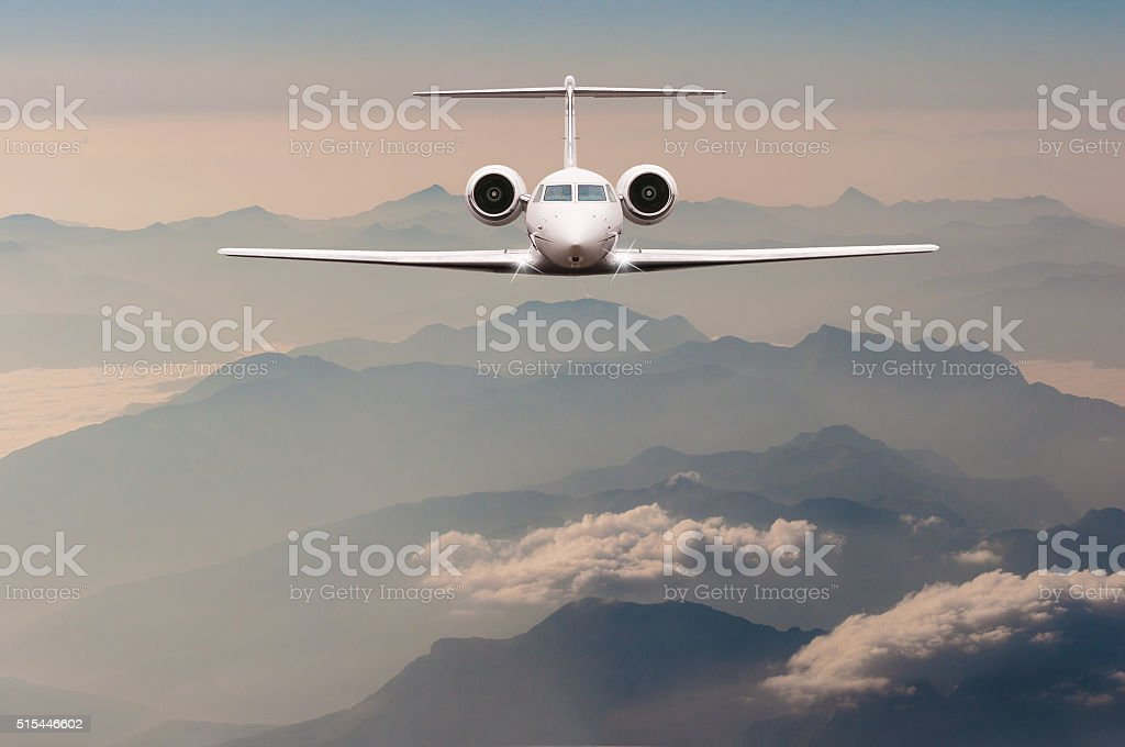 Luxury Airplane fly over clouds and Alps mountain on sunset stock photo