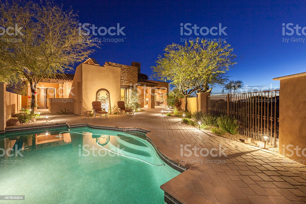 Luxury home backyard pool area in the evening.