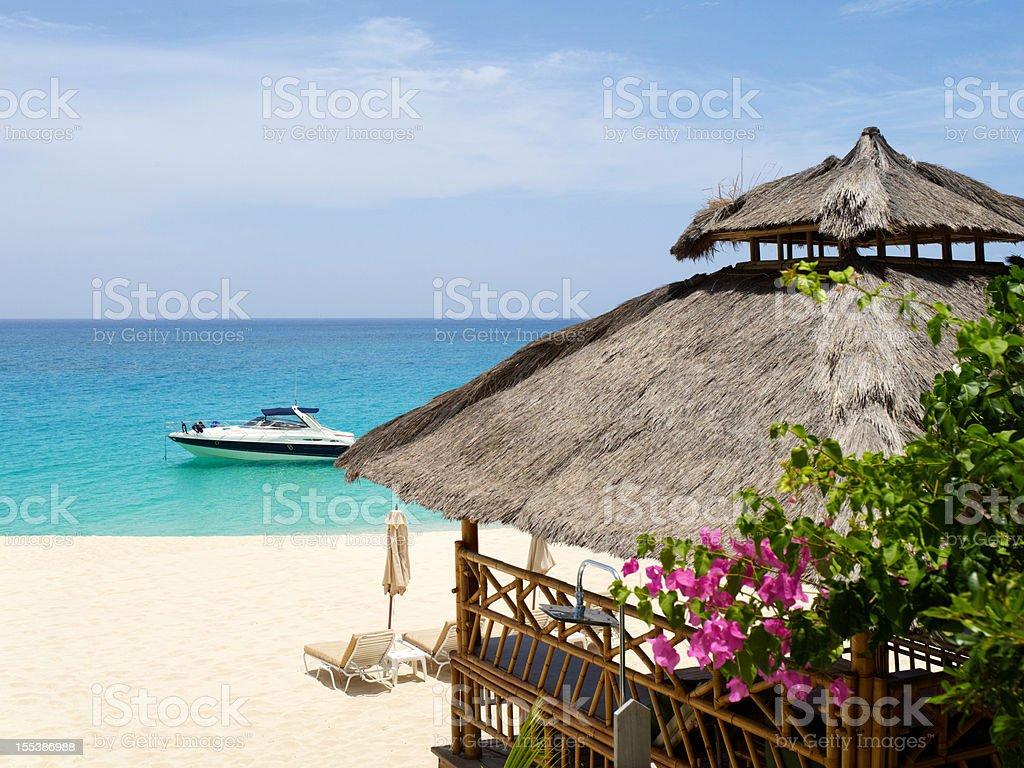 Luxury beach scene with hut and yacht stock photo