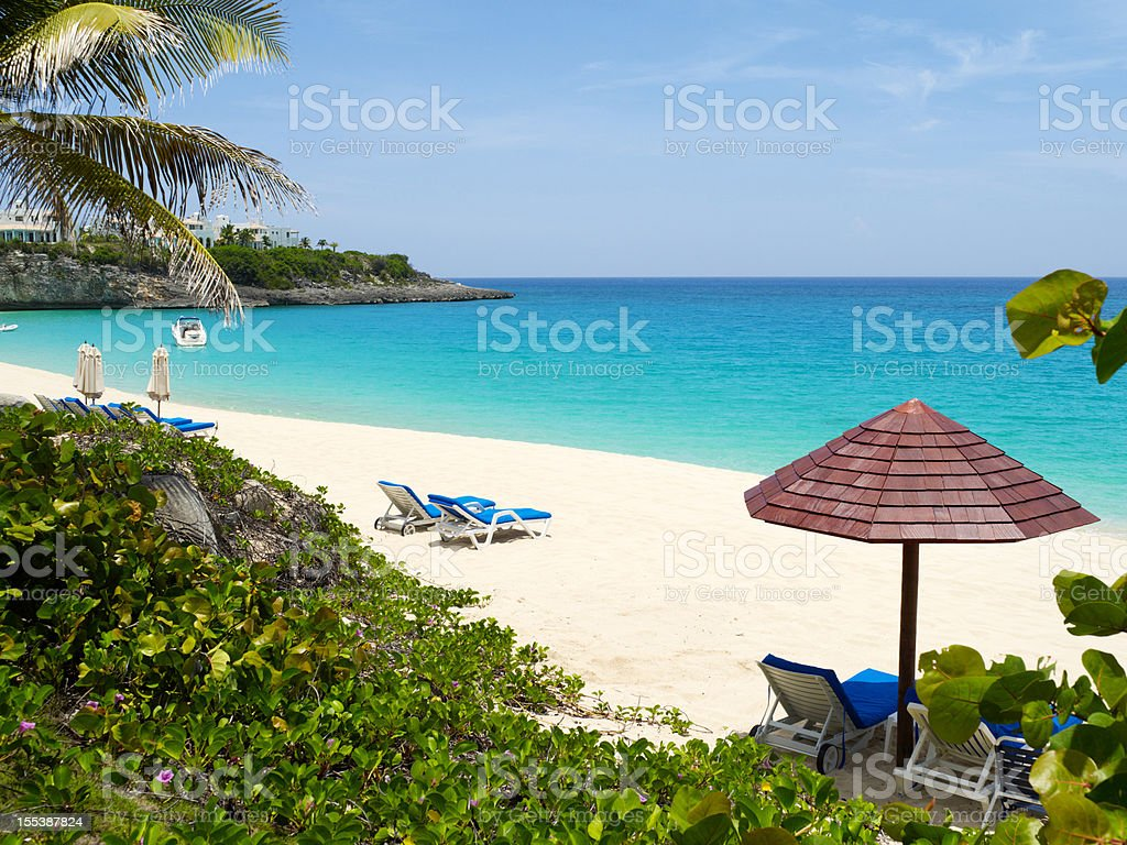 A luxury beach scene with lounge chairs and umbrellas stock photo