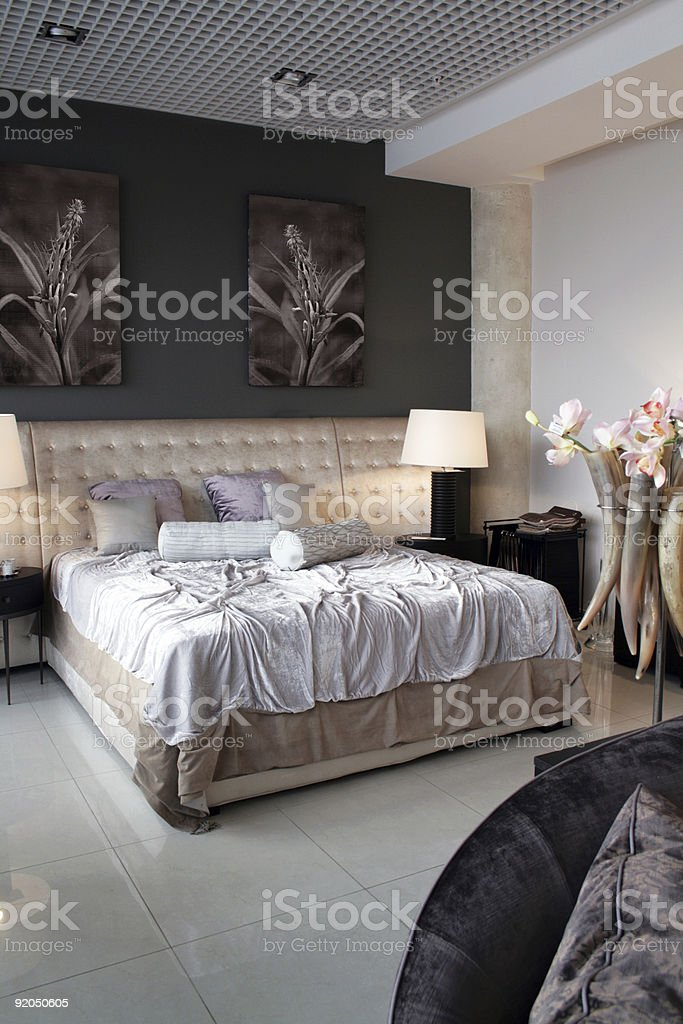 Luxury bedroom with messy bed and tile floors royalty-free stock photo