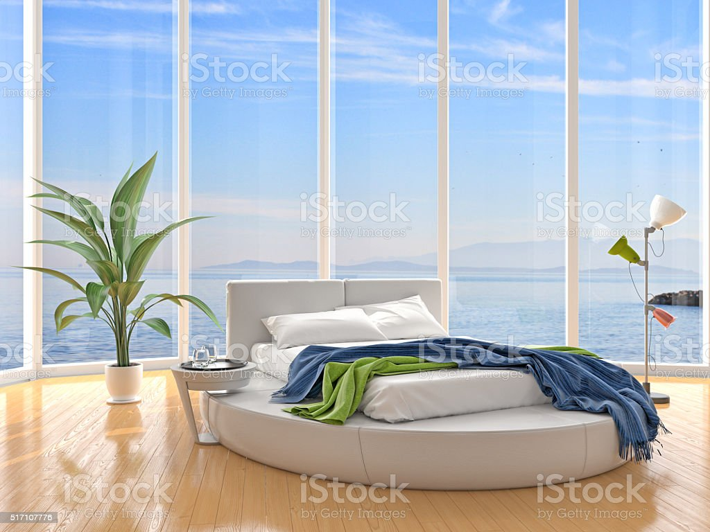 Luxury bedroom with windows on cloudscape the sea stock photo