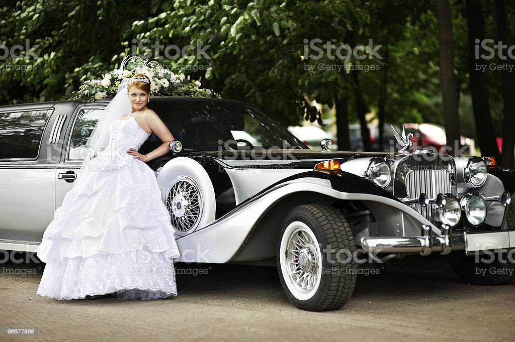 Luxury bride in a wedding dress about retro limousine stock photo