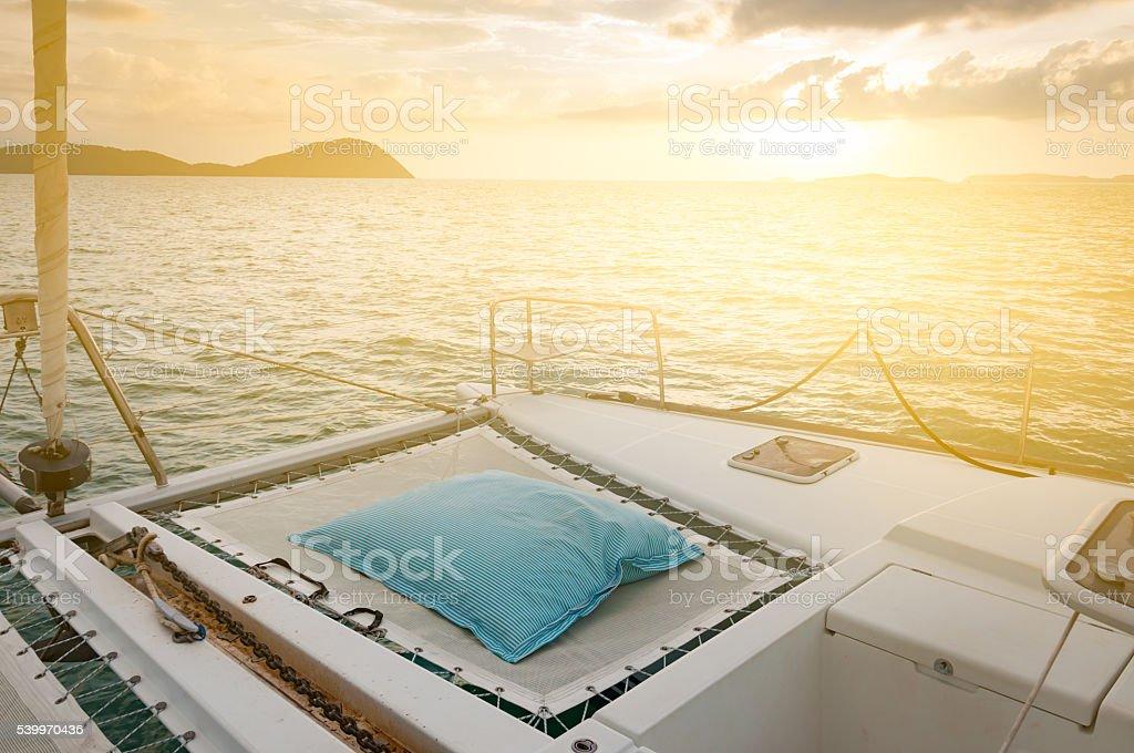 Luxury catamaran yacht deck. Blue and white stripes mattress stock photo
