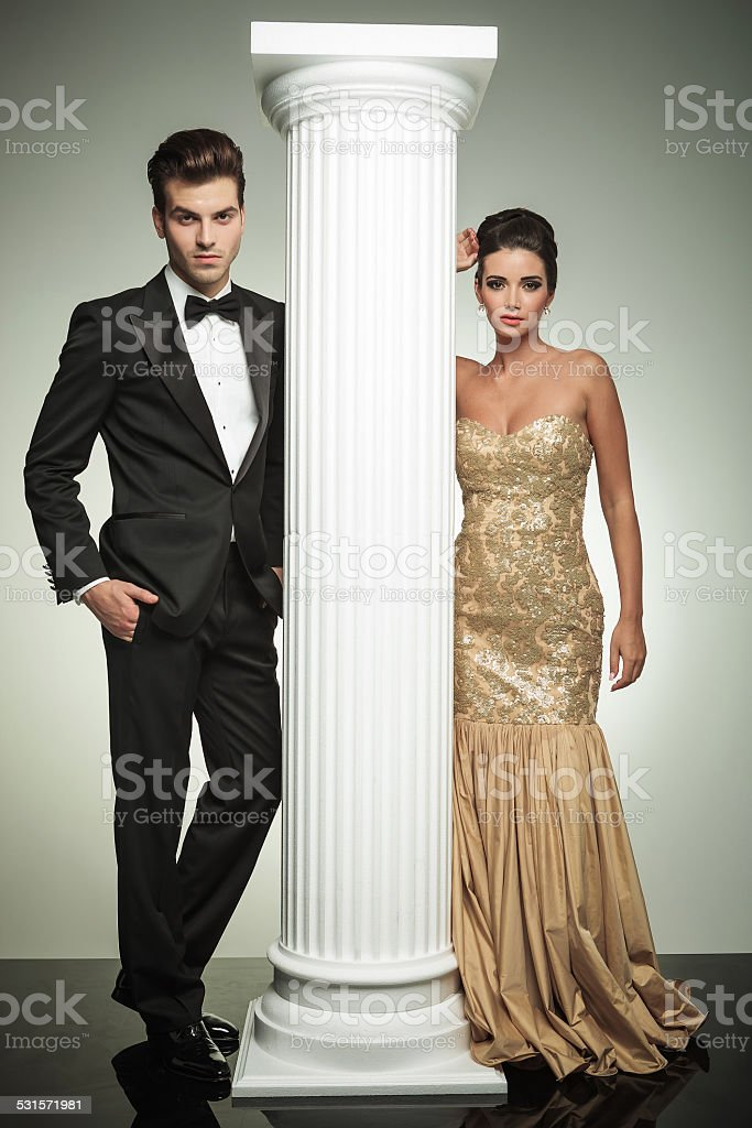 luxury couple posing in studio near column stock photo