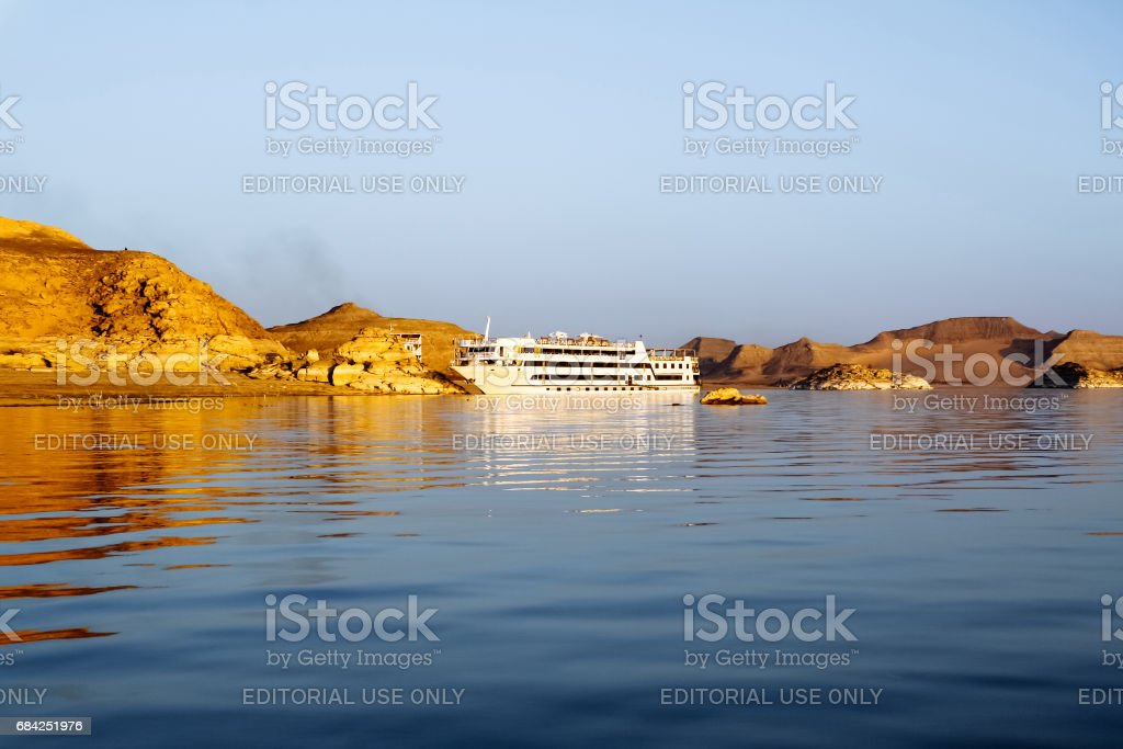 Lake Nasser, Egypt - August 17, 2006: Luxury cruise ship at lake Nasser. The statue of Ramses II and others, at Abu Simbel Temple, look out over Lake Nasser and tourists can enjoy the view from their cruise ship. stock photo