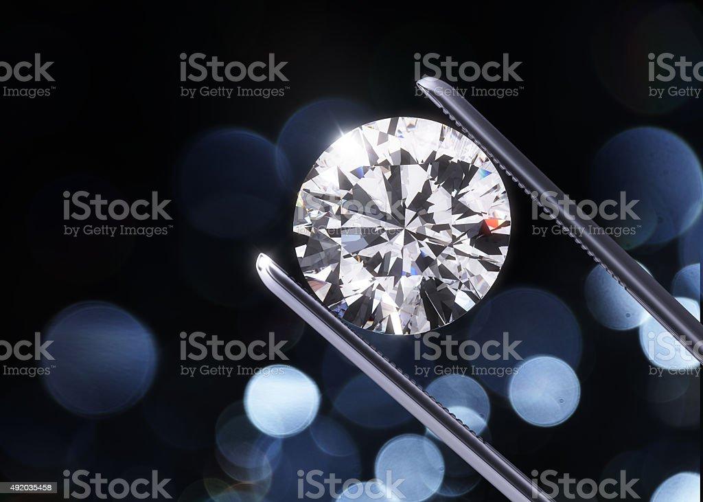 Luxury diamond in tweezers stock photo