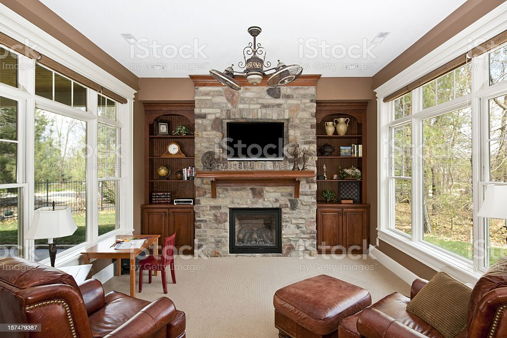 Luxury family room with stone fireplace and window walls stock photo