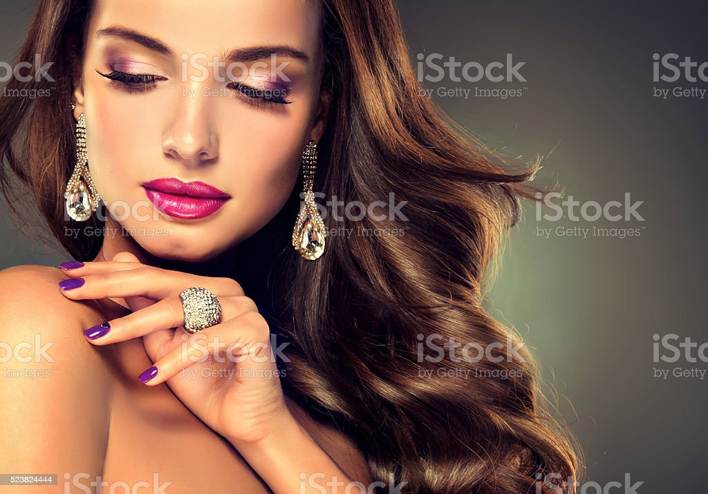 Luxury fashion style.Brunette with long curled hair. stock photo