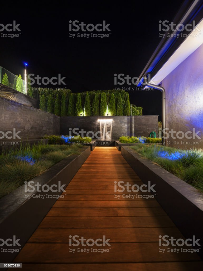 luxury garden with a fountain at night stock photo