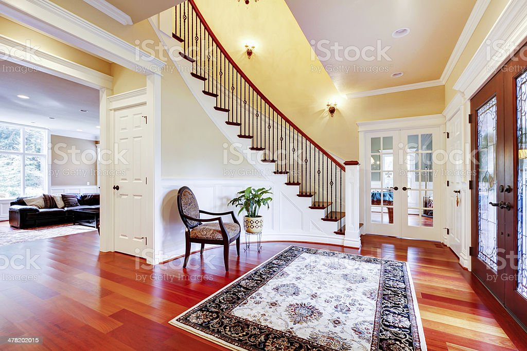 Luxury home entrance with cherry hardwood floor and staircase. stock photo