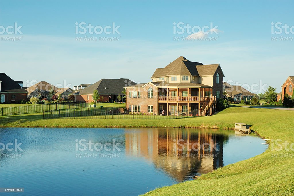 Luxury home neighborhood in front of a still lake stock photo