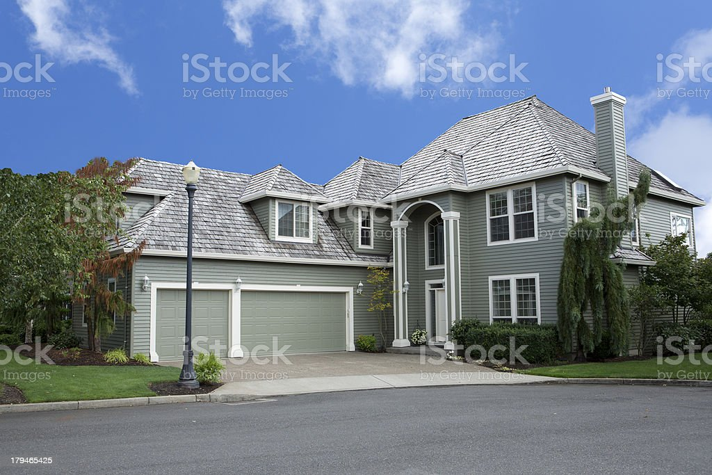 A luxury home pictured against a bright blue sky royalty-free stock photo