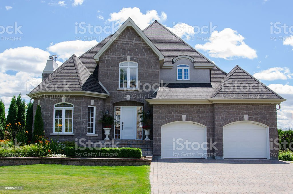 Luxury home with two car garage and landscaped lawn stock photo