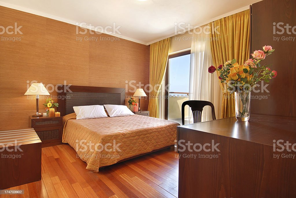 Luxury hotel bedroom with a polished laminate wooden floor. royalty-free stock photo