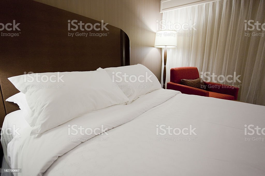 Luxury Hotel Room Bed, Pillows, Lamp, and Chair stock photo