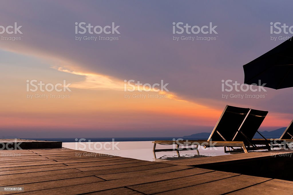 Luxury infinity pool with sunbed and terrace stock photo